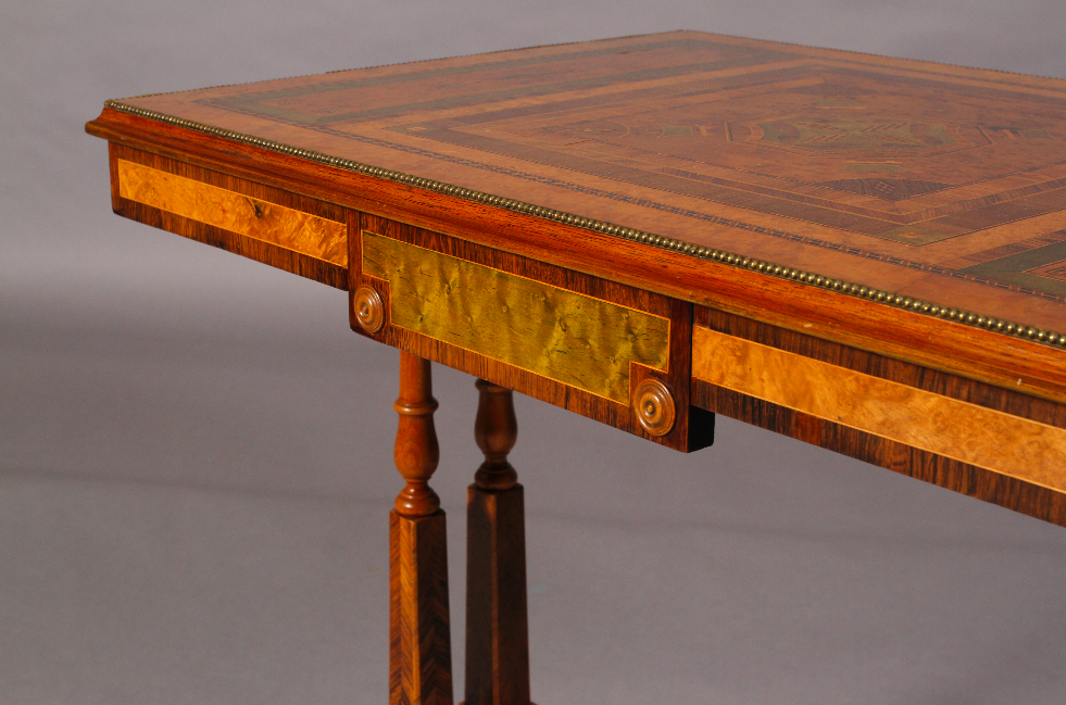 A Regency period walnut and specimen woods rectangular stretcher table.